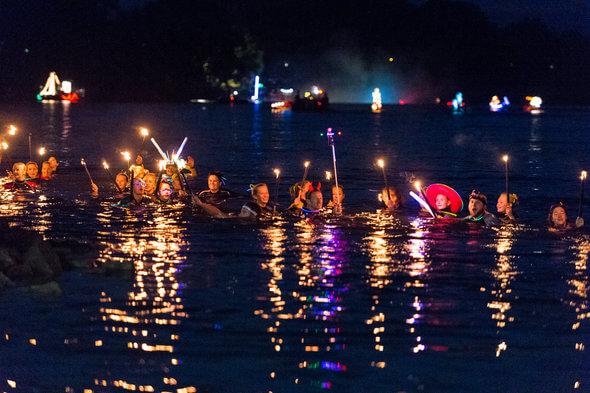 Taucher mit Fackeln schwimmen in der Donau
