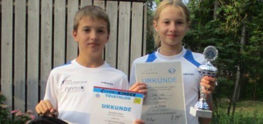 Mädchen und Junge mit Urkunden und Pokal