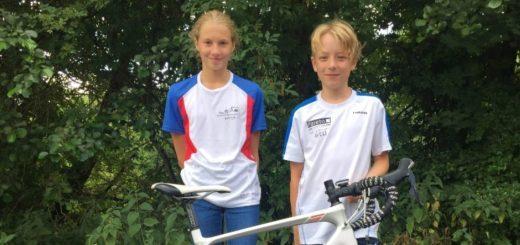 ein Junge und ein Mädchen stehen hinter einem Fahrrad