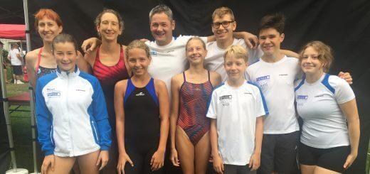 Gruppe junger Schwimmerinnen und Schwimmer mit Trainern