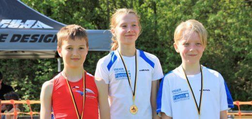 zwei Jungen und ein Mädchen mit Medaillen