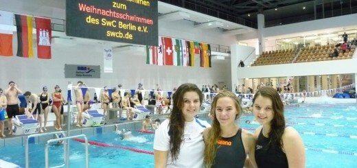 drei Schwimmerinnen lachen in die Kamera - im Hintergrund Schwimmbahnen