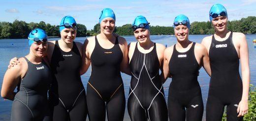 sechs Schwimmerinnen mit schwarzem Badeanzug und blauer Badekappe