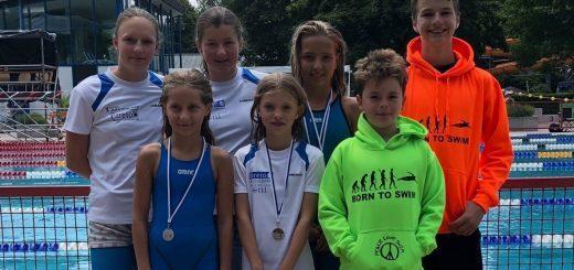 Gruppe junger Schwimmerinnen und Schwimmer mit Medaillen