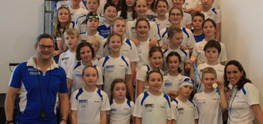 Junge Schwimmerinnen und Schwimmer mit Trainern