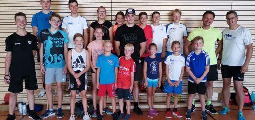 Gruppe junger Schwimmerinnen und Schwimmer und Trainer