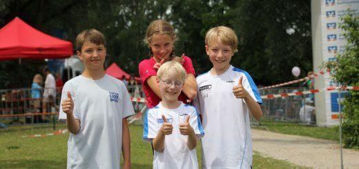 drei Jungs und ein Mädchen schauen in die Kamera